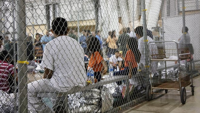 In this Sunday, June 17, 2018 photo provided by U.S. Customs and Border Protection, people who were taken into custody related to cases of illegal entry into the United States, sit in one of the cages at a facility in McAllen, Texas. Border Protection's Rio Grande Valley Sector via AP) ORG XMIT: NY349