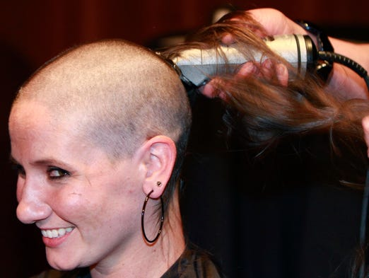 Abby Akin has her head shaved by Sharon Holmes during Shave to Save on Tuesday, July 15, 2014. Akin and seven others had their heads shaved during the event which raised money for the American Cancer Society.