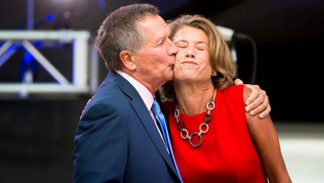 John Kasich embraces his wife Karen in front of a large crowd at an event Ohio's governor hosted at the Rock and Roll Hall of Fame on Tuesday.