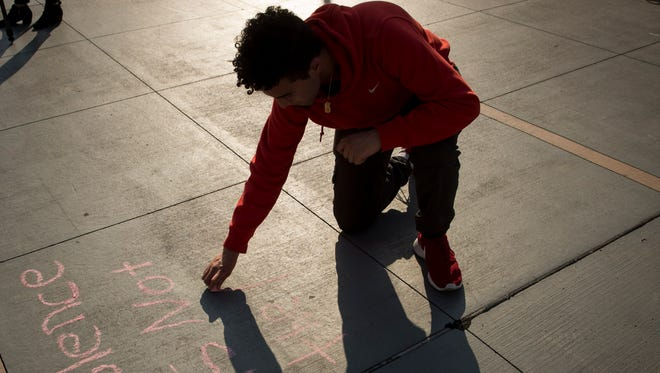"""Kevin Botros, 17, writes """"Violence is not the answer"""" in chalk during a vigil for shooting victims at the Music City Central bus station Tuesday, April 26, 2016, in Nashville. A shooting at the station Monday injured four teenagers."""