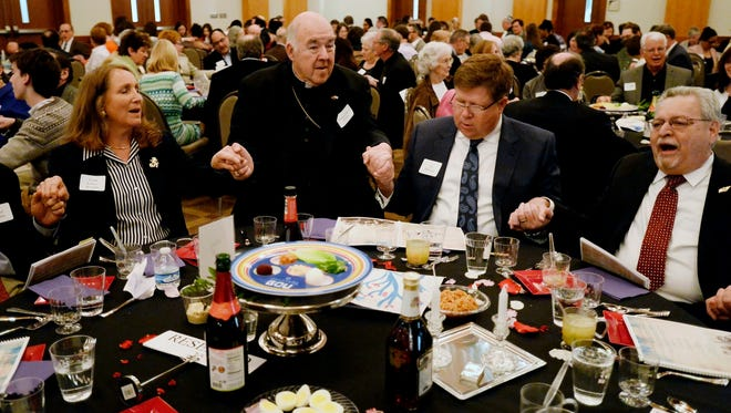 From left, Linda Kartoz Doochin, The Most Reverend David R. Choby and Father Ryan High School President Jim McIntyre sing during the Community Relations Seder celebrating 50 years of reconciliation and improved relations between Catholics and Jews at the Gordon Jewish Community Center on Tuesday, April 12, 2016.