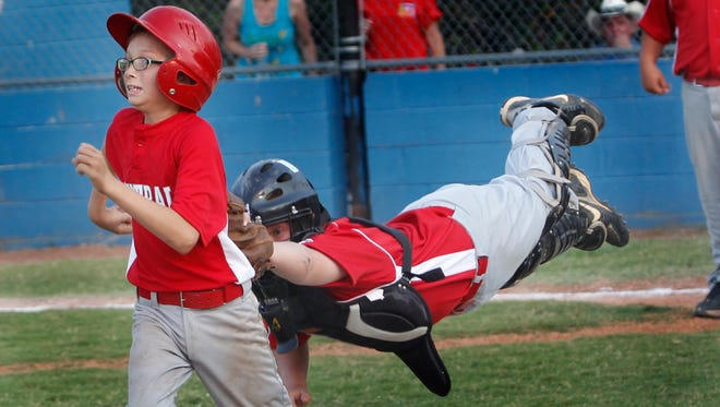 Burns catcher Garrett Wright dives to tag out Central's Bo Perry during the District 9 Little League game at Montgomery Central in June 2012. Central beat Burns 17-7.