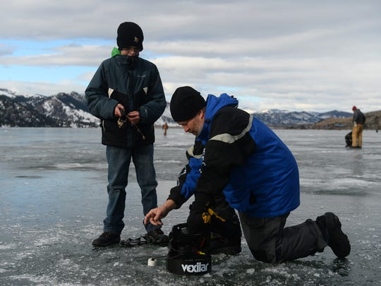 Pat Volkmar, an Industrial Tech teacher at North Middle School, helps Ben Lyons with his line during the Hooked on Fishing Not Drugs ice fishing trip to Holter Lake a few years ago..