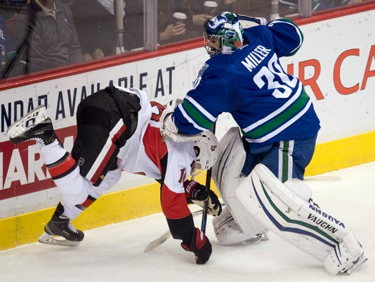 Vancouver Canucks goalie Ryan Miller (30) fights for the puck with Ottawa Senators left wing Clarke MacArthur (16) during the second period of an NHL hockey game Tuesday, Nov. 11, 2014, in Vancouver, British Columbia. (AP Photo/The Canadian Press, Jonathan Hayward)