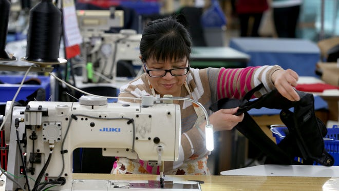 Cai Er Mei prepares to finish a waisbetl strap at Fieldtex Products Inc. in Henrietta for Strong Arm Technologies.