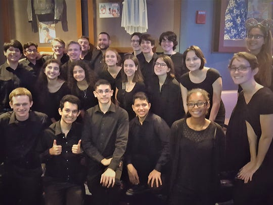 The First Presbyterian Church String Orchestra and Director Jacob Craig pose for a photo after their dinner at Planet Hollywood in Orlando.
