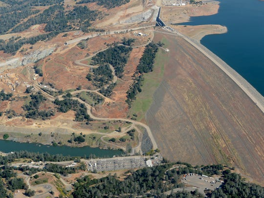 """The Lake Oroville Dam and damaged controlled spillway are seen in May during a flight over the area with Oroville pilot Gonzalo """"Pee Wee"""" Curiel. The authors of a new report are concerned about a green spot on the dam's face that may be vegetation growing with the aid of a water leak."""