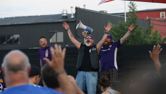 Joe Vala, center, of the Louisville City FC Drum Line, gets the crowd cheering at a rally in support of a new stadium.
