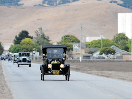 Jim Skillikorn drives his 1915 Ford Model T at the head of a procession of vintage cars out of Spreckels, CA. He is a member of the Horseless Carriage Club of America.