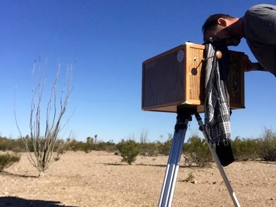 Photographer Nicholas Collier looks through the viewfinder of his custom-made large-format camera while shooting a scene at Big Bend National Park in Texas as part of his artist-in-residence program.