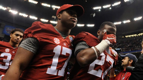 Alabama running back Kenyan Drake (17) and defensive back Nick Perry (27) walk off the field after loosing to Ohio State during the Allstate Sugar Bowl at the Mercedes Benz Superdome in New Orleans, La. on Thursday January 1, 2015.