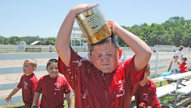 Michael James cools off by pouring a bucket of water on his head during the 2010 Summer Fun camp at Salisbury Baptist Temple.