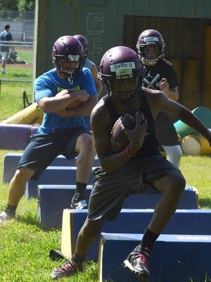 A group of players from Arlington High School's football team runs a drill during preseason practice.