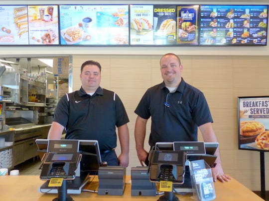 Adam Stokes, left, and brother Dominic, stand ready for business at the counter of their new Taco Bell. In back is a digital menu display.