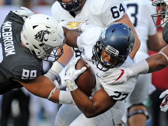 Wolf Pack running back Kelton Moore is stopped for a loss of yardage by Washington State Cougars defensive lineman Garrett McBroom during their game Saturday.