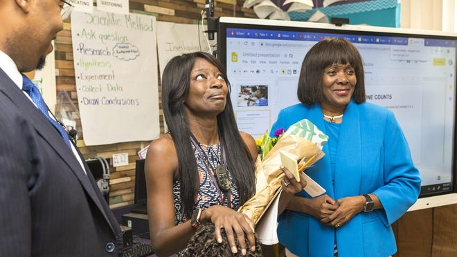 Syndie White, a third grade math, science and social studies teacher at Elbridge Gale Elementary School in Wellington, was surprised by Schools Superintendent Dr. Donald Fennoy as he announced she was the district's Teacher of the Year on March 5.  At right is School Board member Marcia Andrews.