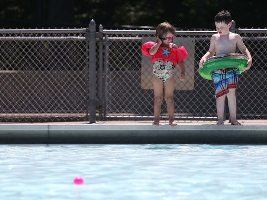 Dylan Best, 5 of Des Moines and Claire Orr, 4 of Saydel contemplate jumping in the water at the Ashworth Pool on Sunday, Aug. 2, 2015 in Des Moines. The Ashworth Pool is the oldest municipal pool in Iowa opening in August 1926.