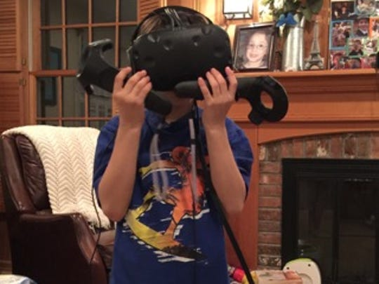 Sam Baig, 9, holds up the Vive headgear with hands.