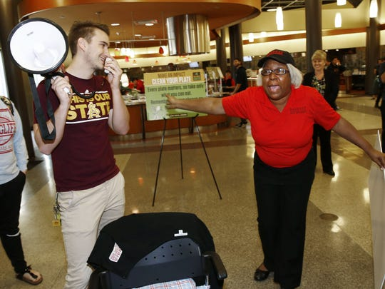 ASU junior Quintin Woods (left) surprises dining room cashier Vicke Davis with a $2,350 check for her dream trip on Jan. 21, 2016, at Barrett, the Honors College at Arizona State University in Tempe.