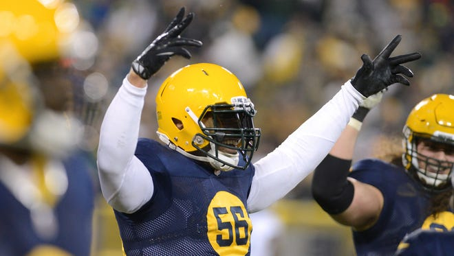 Green Bay Packers linebacker Julius Peppers (56) celebrates his interception returned for a touchdown with teammates.