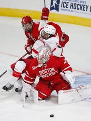 Cornell's Morgan Barron (27) falls on Boston's Jake