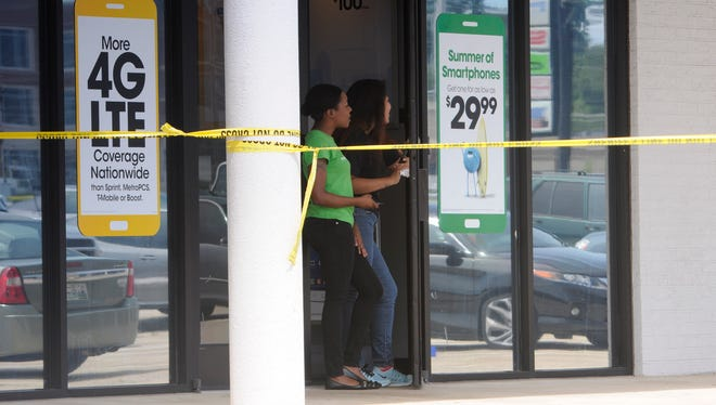 Store employees look out their door next to the Reserve Recruitment Center as the area is cordoned off after a shooting on Thursday, July 16, 2015, in Chattanooga, Tenn.