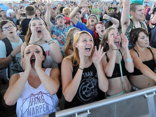 A crowd cheers on Madison band Masked Intruder at the Milwaukee stop of the Vans Warped Tour last year.