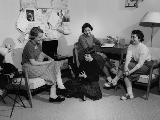 Four women gather in a dormitory room to listen to