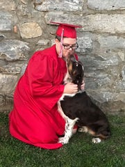 Emily Milam, 18, poses with her dog Cas after graduating.