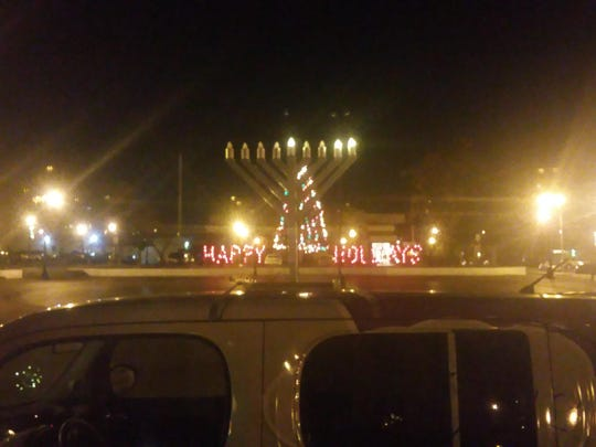 Photo shows small menorah mounted to Harold Herskowitz's car, parked in front of Lakewood's Town Square. Herskowitz is upset that the township removed the menorah from its public holiday display after someone complained.