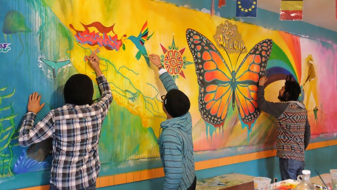 From left, Luis Rodriguez, Juan Carlos Gonzalez and Rudy Jimenez of Urban Arts Collaborative put the finishing touches on a spectacular new mural for Saturday's Art Out Loud benefit for arts education.