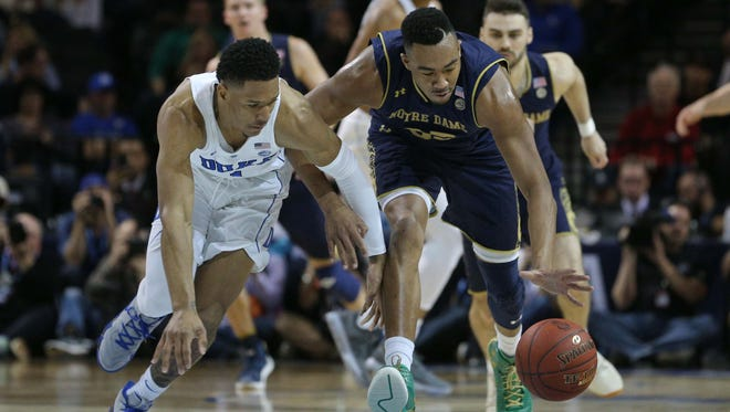 Duke Blue Devils guard Trevon Duval (1) and Notre Notre Dame Fighting Irish forward Bonzie Colson (35) chase a loose ball during the first half of a quarterfinal game of the 2018 ACC tournament at Barclays Center.