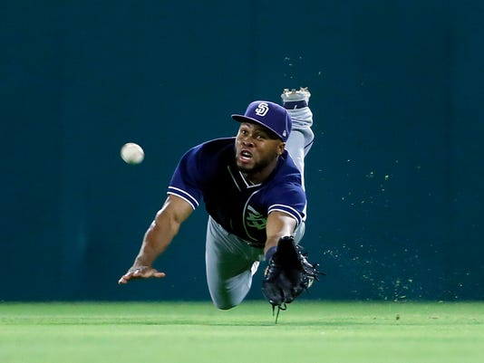 San Diego Padres center fielder Manuel Margot dives but is unable to reach a single by Texas Rangers' Jonathan Lucroy during the ninth inning of a baseball game, Thursday, May 11, 2017, in Arlington, Texas. (AP Photo/Tony Gutierrez)