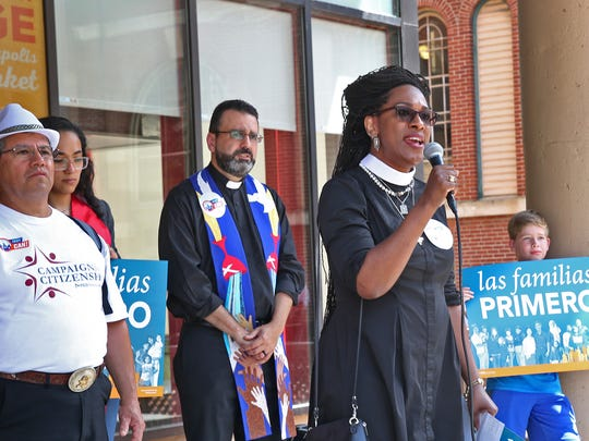 "Priest Shannon MacVean-Brown sings ""Oh Freedom"" during a 2017 vigil and march calling on local law enforcement to stop supporting unlawful detentions of undocumented immigrants by Immigration and Customs Enforcement, in Burlington, Vt."