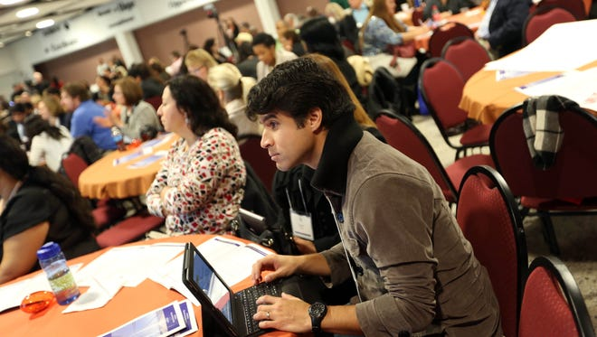 Carlos Reyes-Rodriguez, 31, of Dover, takes notes while listening to speakers at the inaugural 2014 Delaware Latino Summit at Delaware Technical Community College's Terry Campus in Dover.