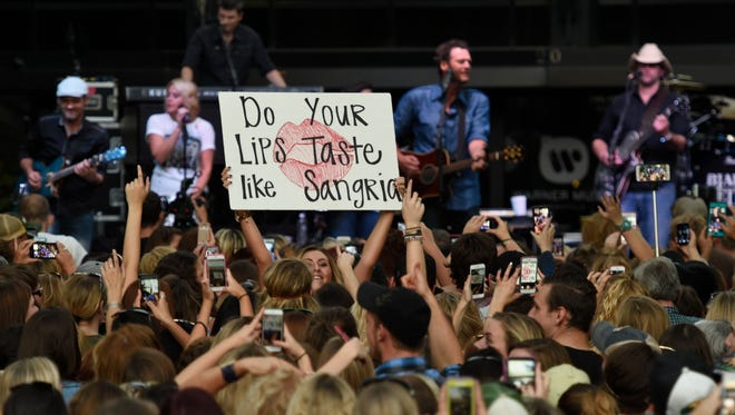 Blake Shelton fans hold up signs as Shelton performs outside Warner Bros. records on 16th Ave. shutting down several blocks in the Music Row area for a free concert Wednesday Sept. 23, 2015, in Nashville, Tenn.