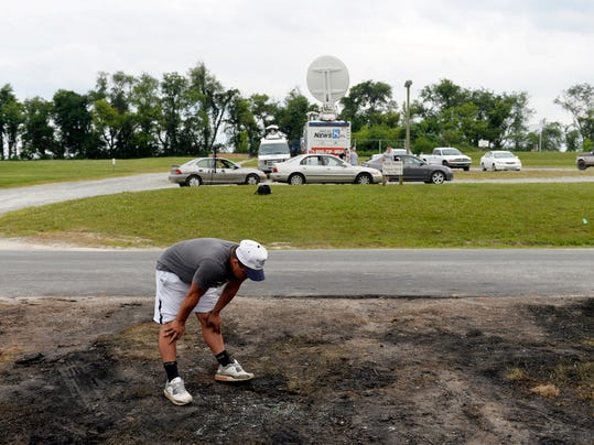 Red Lion rising junior Dylan Gurreri examines the charred ground at the site of a car crash that claimed the lives of two Red Lion Area High School rising seniors, Stone Hill, 17, and Nick Mankin, 16.