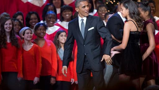 President Barack Obama, from left, and his daughters Malia Obama and Sasha Obama,  leave the stage at the conclusion of the taping of the annual 2014 Christmas in Washington presentation at the National Building Museum in Washington, Sunday.