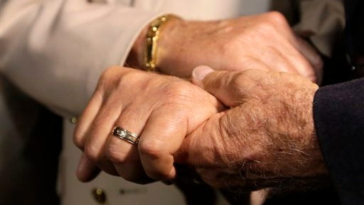 Charles Hunziker, 83, left, and Bob Collier, 80, right, of Fort Lauderdale, Fla., hold hands during a renewal of wedding vows ceremony held by the SAVE Foundation, a LGBT rights group, Tuesday, Jan. 6, 2015, in Miami Beach, Fla.