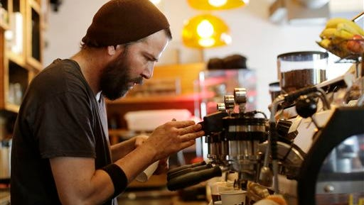 In this Thursday, June 4, 2015,  photo, employee J.P. Aristizabal prepares coffee drinks at Panther Coffee, independently owned coffee retailer and wholesaler, in Miami. The Commerce Department releases retail sales data for May on Thursday, June 11, 2015. (AP Photo/Lynne Sladky)