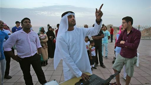 In this Tuesday June 16, 2015 photo, people of different nationalities listen to Nezar Hezam, Chairman of the Emirates Mobile Observatory, center, as they take part in a moon sighting event on top of Jebel Hafeet mountain to mark the beginning of the holy month of Ramadan in Al Ain, United Arab Emirates. The sighting of the new moon marks the beginning of Ramadan. (AP Photo/Kamran Jebreili)