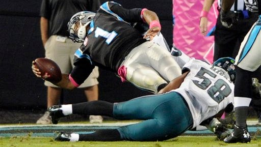 Carolina Panthers' Cam Newton (1) leans over the goal line for a touchdown as Philadelphia Eagles' Jordan Hicks (58) defends in the first half of an NFL football game in Charlotte, N.C., Sunday.