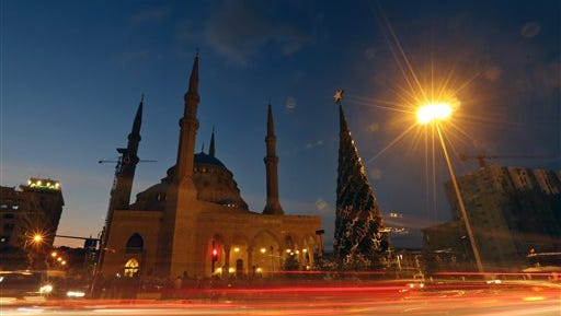 In this photo made with a slow shutter speed to show motion, people gather during the illumination of a giant Christmas tree at the launch of 2015 Christmas festivities, in front of Muhammad al-Amin Mosque in Beirut, Lebanon, Friday, Dec. 11, 2015.