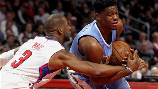 Los Angeles Clippers guard Chris Paul (3) reaches in for the ball against Denver Nuggets guard Emmanuel Mudiay, right, during the second half of an NBA basketball game in Los Angeles, Wednesday, Feb. 24, 2016. The Nuggets won 87-81. (AP Photo/Alex Gallardo)