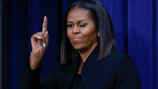 First lady Michelle Obama 'winks' and gestures to guests after after speaking following the screening for the movie 'Hidden Figures,' Thursday, Dec. 15, 2016, in the South Court Auditorium in the Eisenhower Executive Office Building on the White House complex in Washington.