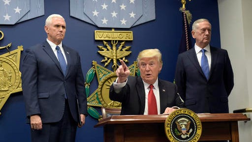 President Donald Trump, center, gestures after signing two executive action at the Pentagon in Washington, Friday, Jan. 27, 2017, with Vice President Mike Pence, left, and Defense Secretary James Mattis, right, at his side.