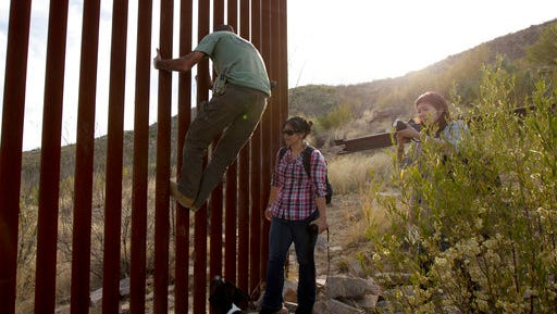 FILE - In this May 11, 2016, file photo, Tim Foley shows how to climb a section of the border wall separating Mexico and the United States near where it ends as journalists Chitose Nakagawa, right, and Marcie Mieko Kagawa look on in Sasabe, Ariz. Foley, a former construction foreman, founded Arizona Border Recon, a group of armed volunteers who dedicate themselves to border surveillance. With bids due Tuesday, April 4, 2017, on the first border wall design contracts, companies are preparing for the worst if they get the potentially lucrative but controversial job.