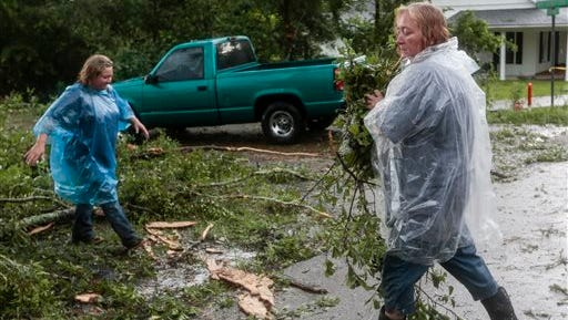 Gretel Morales, left, works to clear debris from the roadway today in Liberty.