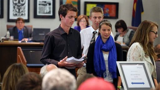 Evergreen high school students, left to right, Eric Temple, Chalen Gordon-Mcglone, Caitlin Schmitt, and Mali Holmes walk back to their seats after testifying during an ongoing Jefferson County School Board meeting, strongly protesting the school board's proposal to emphasize patriotism and downplay civil unrest in the teaching of U.S. history, in Golden, Colo., Thursday.