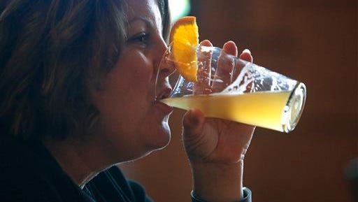 Stacey Tilbury of Portage, Mich., drinks a glass of Bell's Oberon at the Eccentric Cafe in Kalamazoo Monday, March 24, 2014.